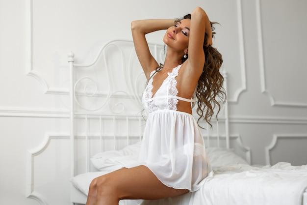 ベッドの上の化粧と髪型を持つ美しい若い女性