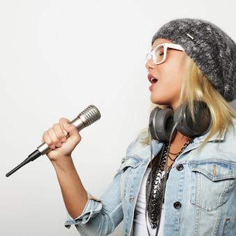 Красивая молодая женщина с микрофоном и наушниками на сером фоне