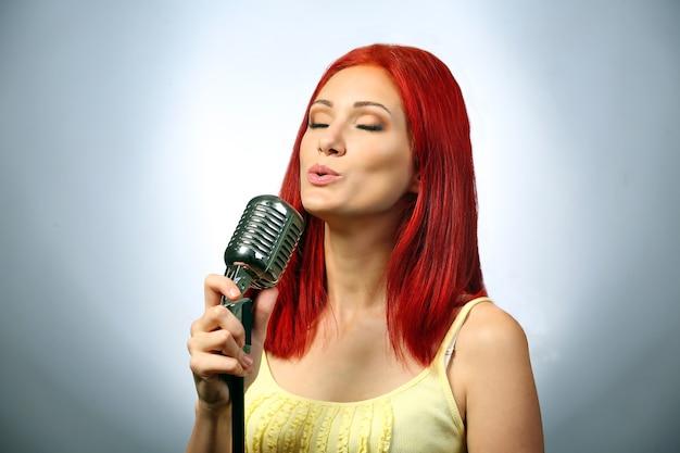 Красивая молодая женщина с микрофоном на сером фоне
