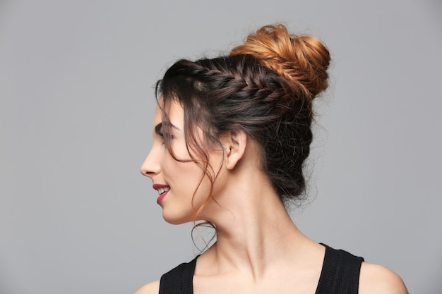 灰色の背景にモダンな髪型の美しい若い女性