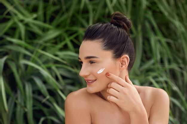 顔に保湿クリームを持つ美しい若い女性。
