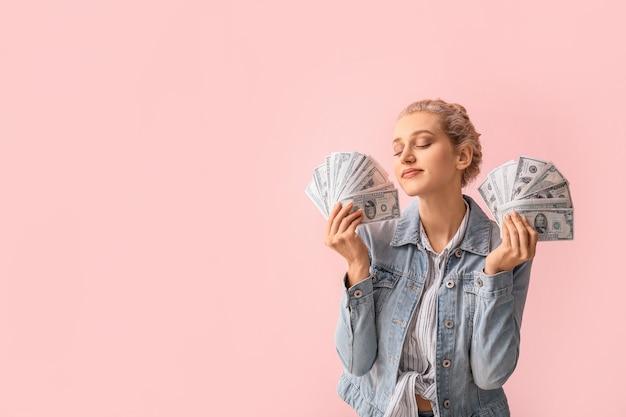 色の背景にお金を持つ美しい若い女性
