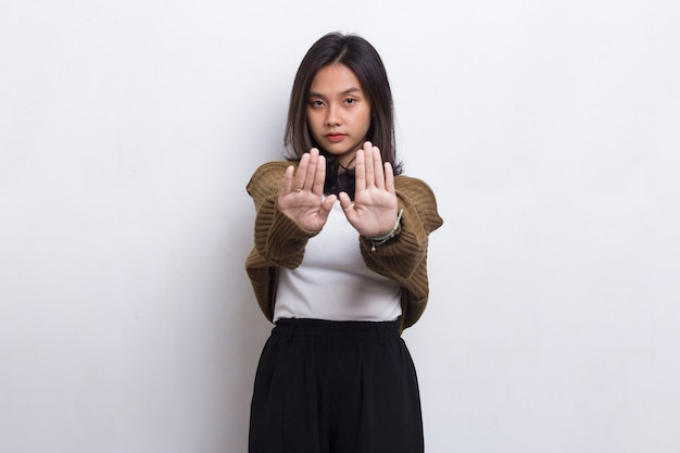 Beautiful young woman with open hand doing stop sign with serious expression defense gesture