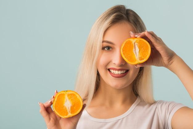 手でオレンジ色の美しい若い女性