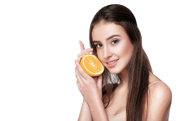 Beautiful young woman with orange isolated on white background. healthy food