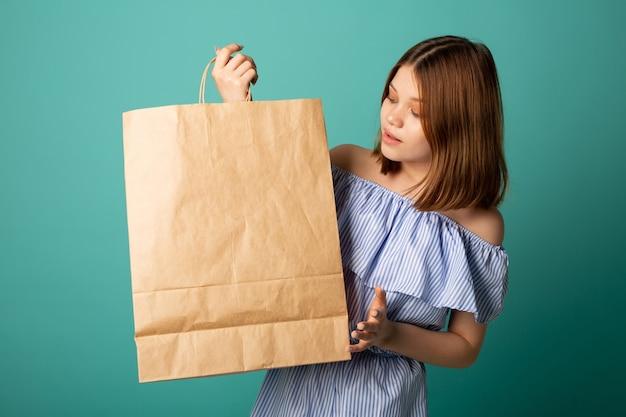 놀란 얼굴로 손에 종이 봉지를 들고 있는 아름다운 젊은 여성