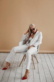 スタジオでポーズをとってエレガントな白いスーツと赤い靴で完璧なブロンドの髪を持つ美しい若い女性。