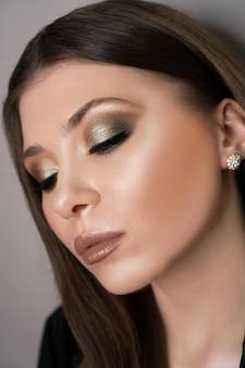 Красивая молодая женщина с идеальной чистой кожей, ярким сияющим изумрудным модным макияжем