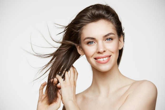 흰 벽에 머리를 만지고 웃 고 완벽 한 깨끗 한 피부와 아름 다운 젊은 여자. 페이셜 트리트먼트.