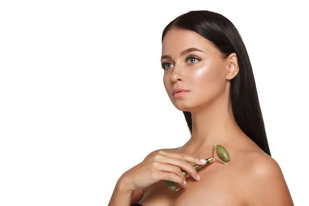 Красивая молодая женщина с идеальной кожей в полотенце на голове, используя нефритовый валик для лица с натуральными кварцевыми камнями на белом