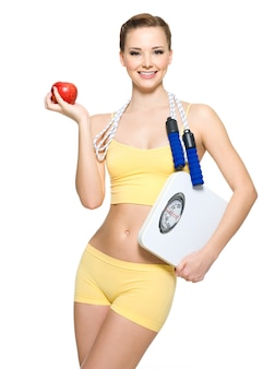 Beautiful young woman with perfect sporty body holding scales and apple