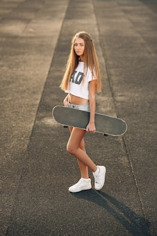 Beautiful young woman with piercing in a white t-shirt, shorts and white sneakers standing with skateboard in hands