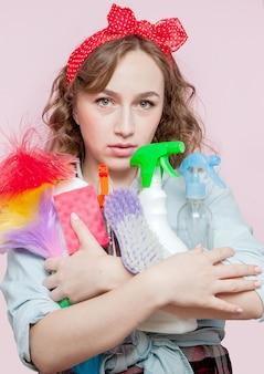 Красивая молодая женщина с макияжем и прической пин ап с чистящими средствами на розовом фоне.