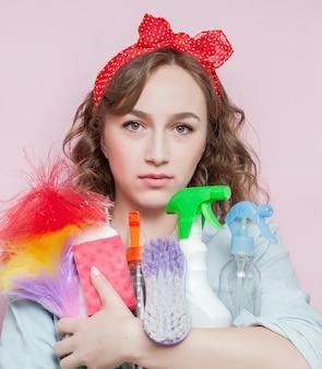 Красивая молодая женщина с макияжем в стиле пин-ап и прической с чистящими средствами на розовом фоне