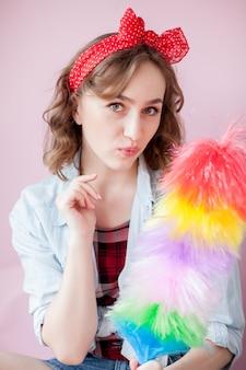ピンのメイクアップとクリーニングツールと髪型と美しい若い女性
