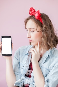 Beautiful young woman with pin-up make-up and hairstyle over pink background with mobile phone with copy space.