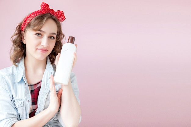 Beautiful young woman with pin-up make-up and hairstyle with cleaning tools on pink wall