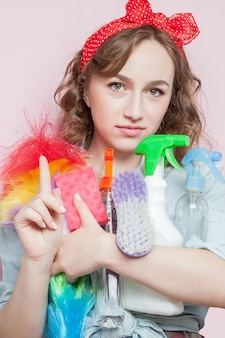 Beautiful young woman with pin-up make-up and hairstyle with cleaning tools on pink.