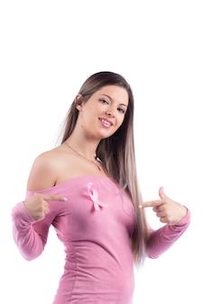 乳がんのピンクの意識リボンとピンクのドレスの美しい若い女性。