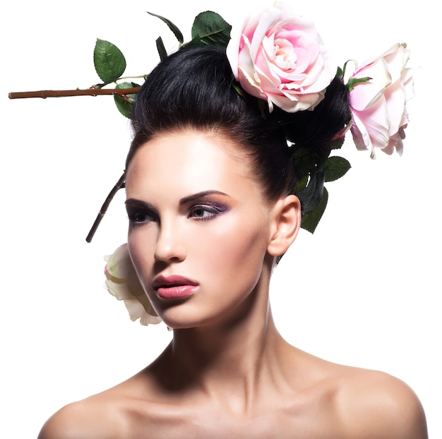 Bella giovane donna con fiori rosa nei capelli - isolato su bianco.