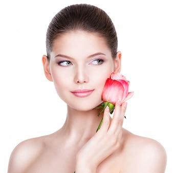 ピンクのバラの美しい若い女性。美容トリートメントのコンセプト。白い壁の上の肖像画。