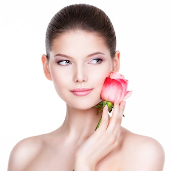Beautiful young woman with pink rose. beauty treatment concept. portrait over white wall.
