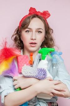 Красивая молодая женщина с макияжем кинозвезды и прической с чистящими средствами на розовом.