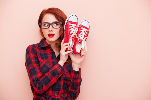 Beautiful young woman with red gumshoes on the wonderful pink background