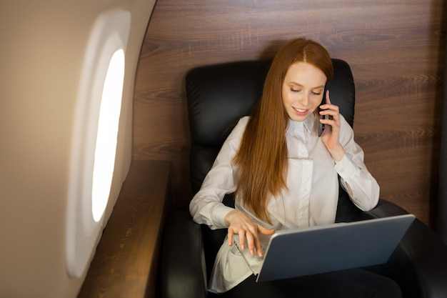 Beautiful young woman with red hair in the cabin of the plane with a laptop