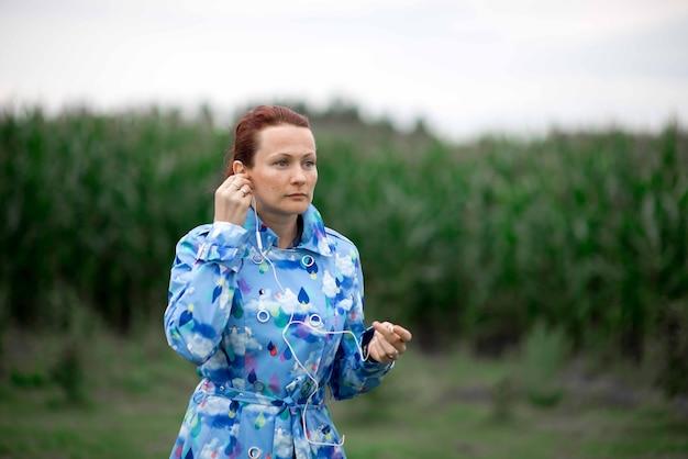 ヘッドフォンで音楽を聴いている赤い髪の美しい若い女性