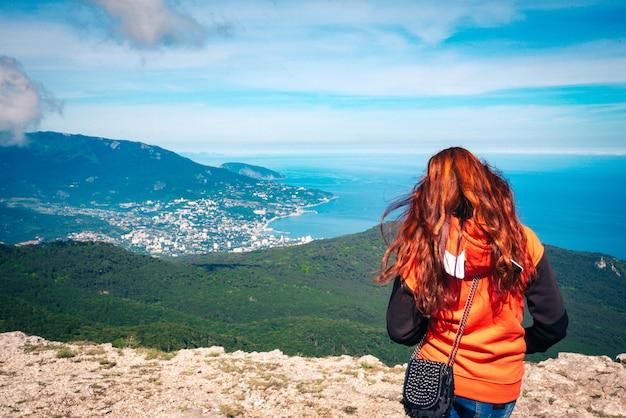 Красивая молодая женщина с рыжими волосами на горе смотрит на море. панорамный вид с воздуха на город ялта в крыму, россия.