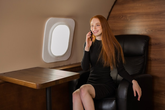 Beautiful young woman with red hair talking on the phone in the cabin of a private jet