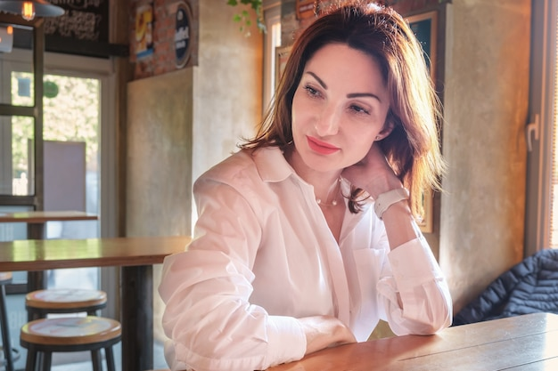Beautiful young woman with red hair in a white shirt sits at a wooden table in a bar and is thoughtful. young woman portrait. woman waiting for a meeting.