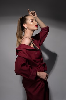 A beautiful young woman with red lips and a high tail in a burgundy raincoat and a black bra.