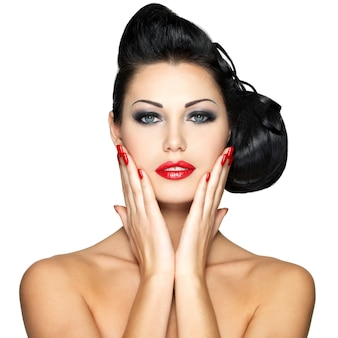 Beautiful young woman with red nails and fashion makeup