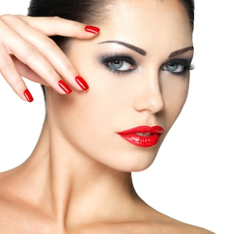 Bella giovane donna con unghie rosse e trucco moda