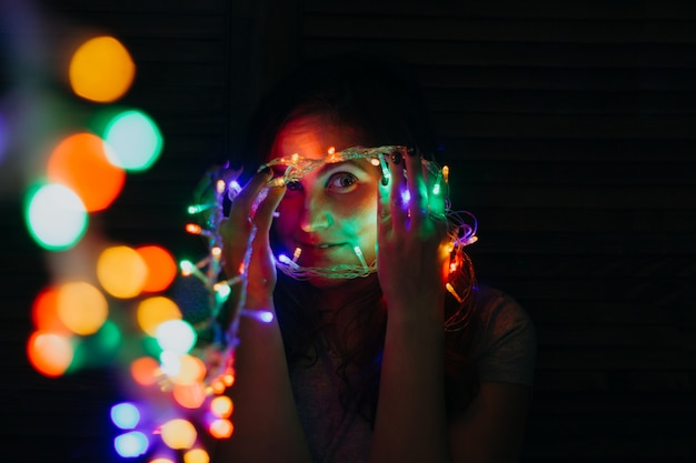 Beautiful young woman with shining garland lights
