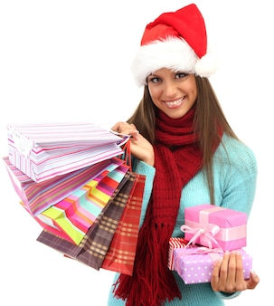 Beautiful young woman with shopping bags and gifts, isolated on white