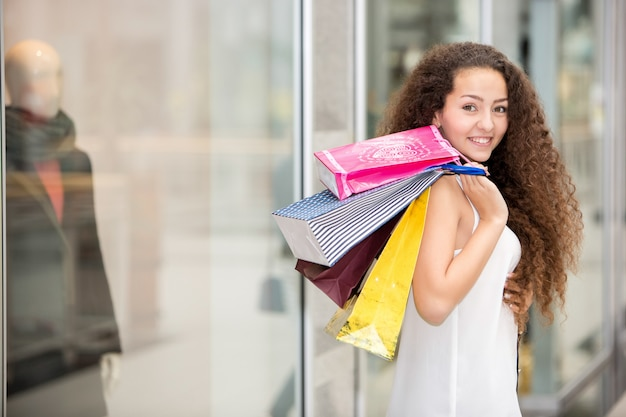 Bella giovane donna con i sacchetti della spesa nel centro commerciale