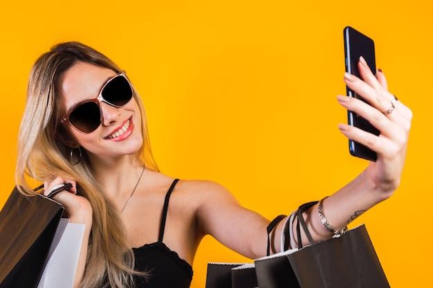 노란색 배경에 셀카를 찍는 쇼핑백을 든 아름다운 젊은 여성. 검은 금요일.