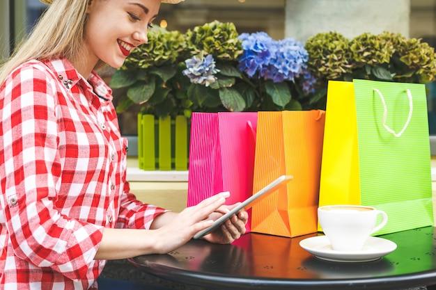 옷 가게에 서있는 동안 미소로 그녀의 노트북 컴퓨터를 사용하는 쇼핑백과 아름 다운 젊은 여자