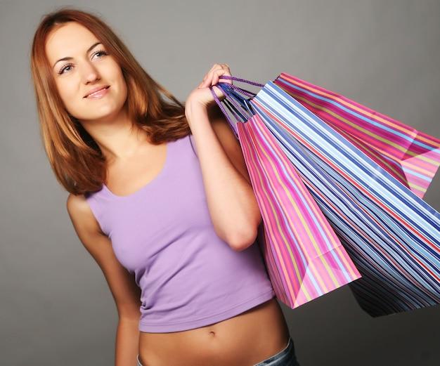 Красивая молодая женщина с хозяйственными сумками