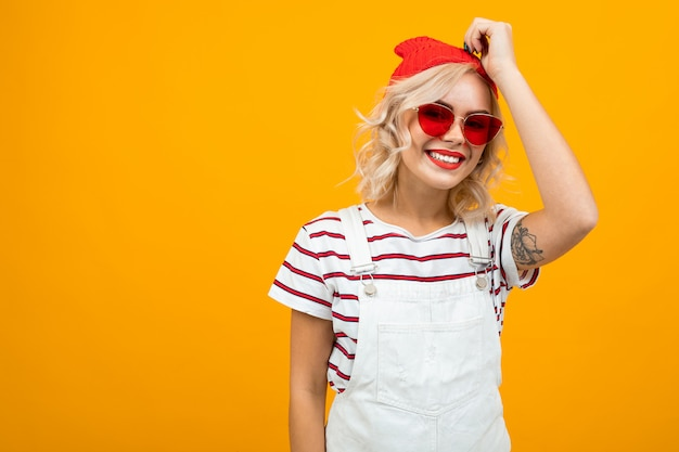 Beautiful young woman with short blonde curly hair and bright makeup in white overalls. red sunglasses and red hat gesticulated and smiles, portrait isolated on orange
