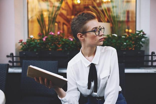 カフェのテーブルで彼女の手に本を持った眼鏡の短い髪の美しい若い女性