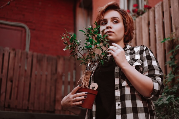 Beautiful young woman with short red hair in a plaid shirt holding a flower in a pot in the backyard