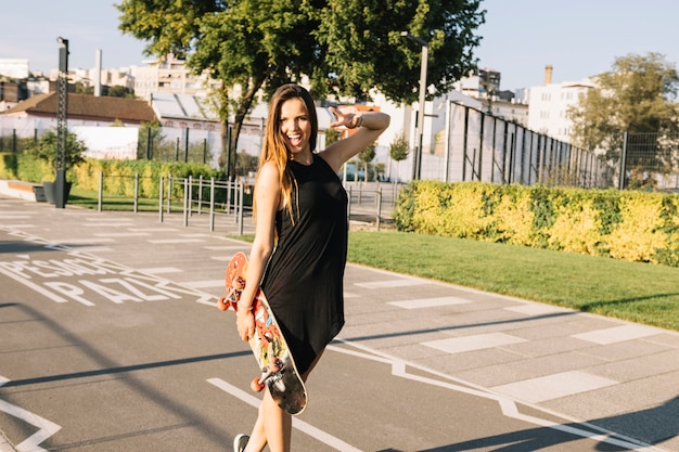 Beautiful young woman with skateboard standing on street