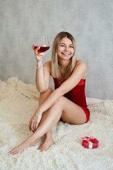 A beautiful young woman with smile is sitting in red underwear on a white plaid with wine in her hand. valentines day morning. vertically photo