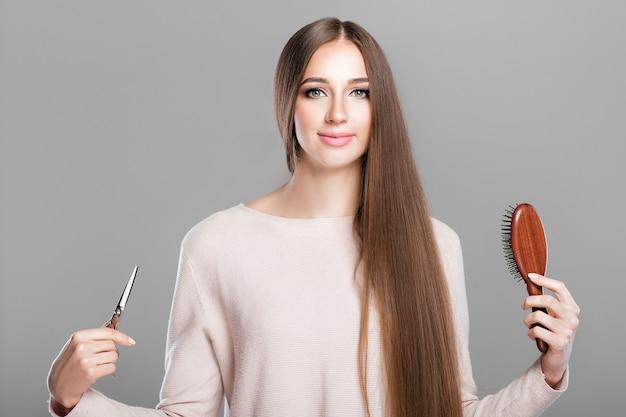 Красивая молодая женщина с гладкими длинными натуральными волосами держит расческу и ножницы