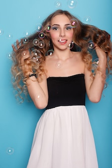 Beautiful young woman with soap bubbles over cyan background. portrait of young beautiful girl in studio, with professional makeup. beauty shooting. the beauty of soap bubbles.