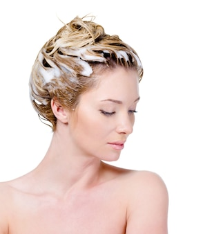 Красивая молодая женщина с мыльной головой и закрытыми глазами, изолированными на белом